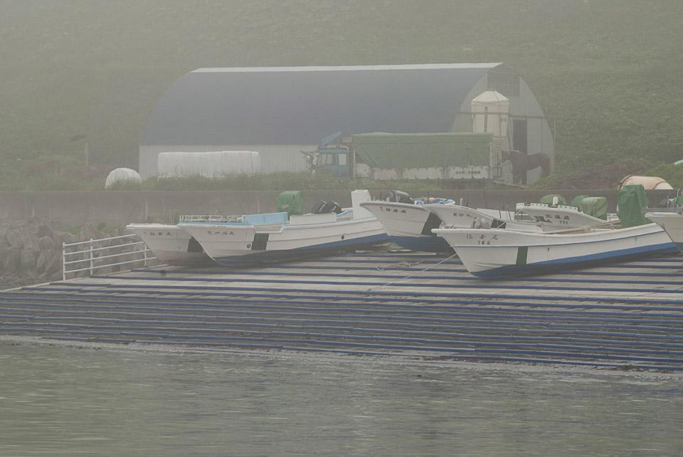 Im Hintergrund eine Lagerhalle. Nebel liegt zwischen den Hügeln, es ist feucht.