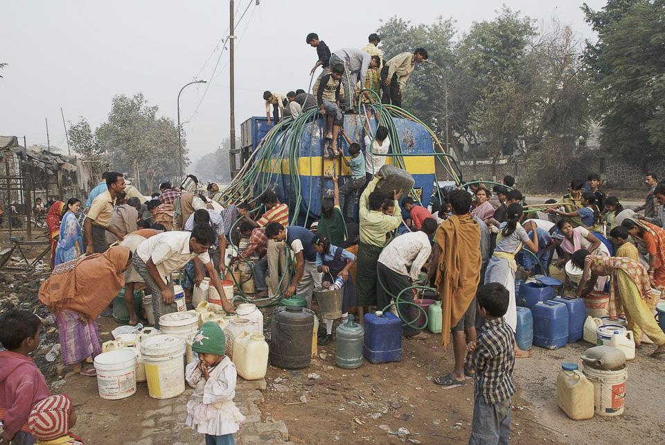 Früh kommt der städtische Wasserwagen.   Die Bewohner des Slumviertels bringen Kanister, Eimer und Schläuche.  