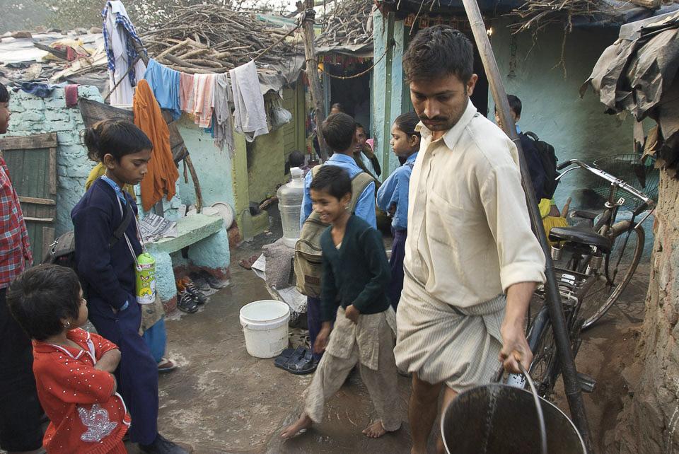 Der Tag beinnt um 5 Uhr früh im Slum von Vasant Kunj, New Delhi.   Im informellen Wohngebiet von Vasant kunj holen die Bewohner Wasser um 6.30h morgens vom öffentlichen Wasserwagen.  