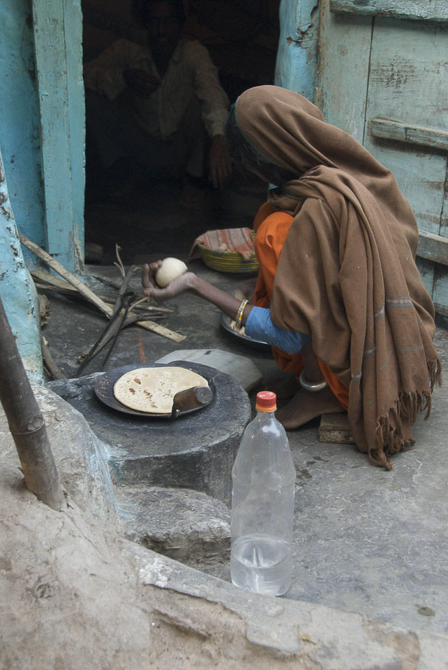 Arbeit der Frauen morgens um 6 Uhr. | Im Inneren des Hauses warten Familienmitglieder auf das Frühstück. |