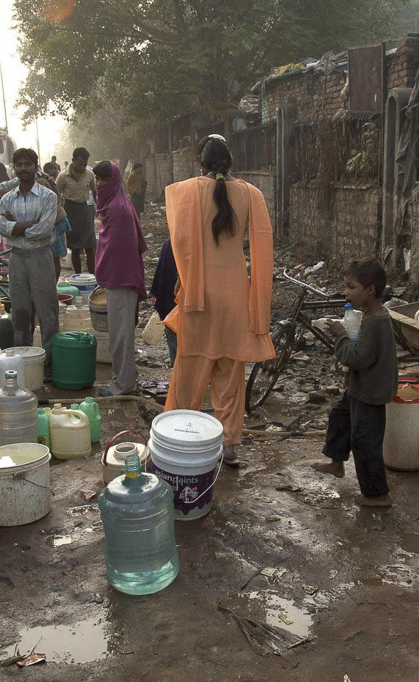Morgens um 6h in der Früh, Slum von Vasant Kunj   Auf der Straße vor dem Slum. Morgens um 6 h geht die Bewohnerin des Slums zur Arbeit. Viele aus dieser Siedlung arbeiten bei den wohlhabenderen Familien.  